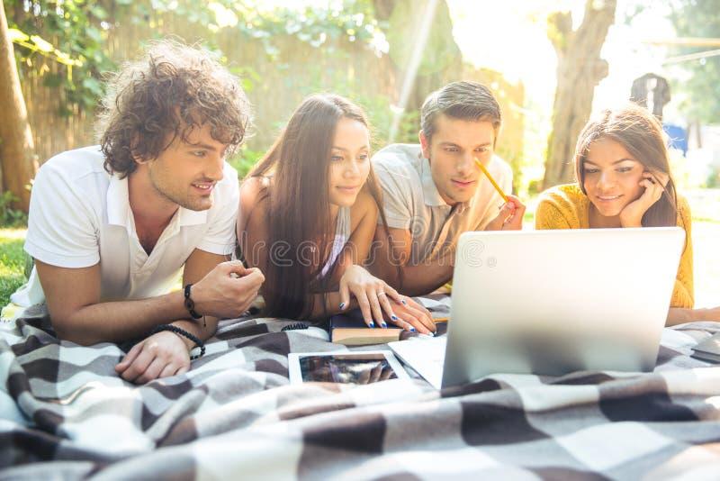 Studenten die thuiswerk op laptop samen doen stock afbeeldingen