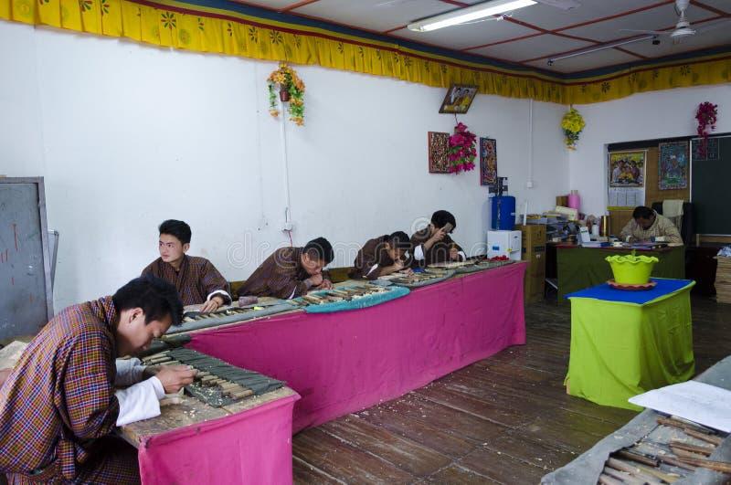 Studenten die traditioneel houtsnijwerk leren Uit Bhutan stock afbeelding