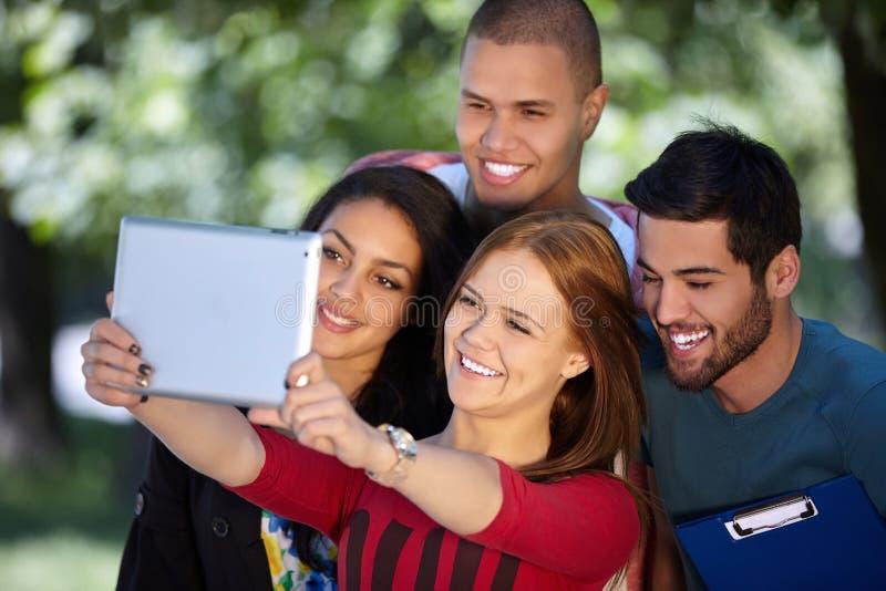 Studenten die uit en selfie in een park nemen hangen stock foto's