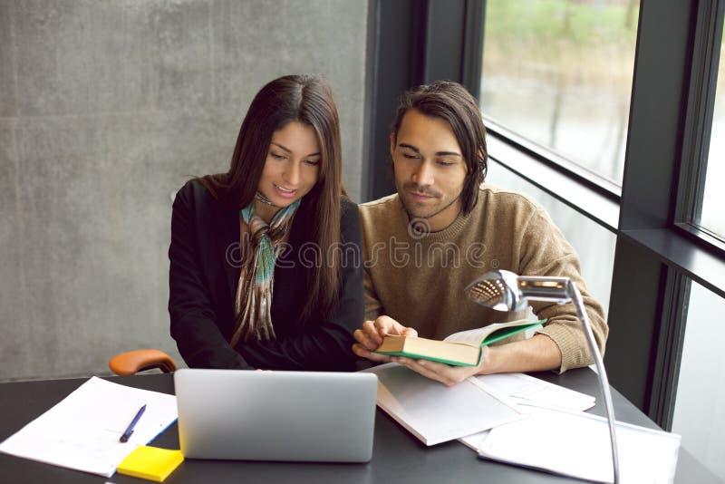 Studenten die voor examens samen in bibliotheek voorbereidingen treffen royalty-vrije stock foto