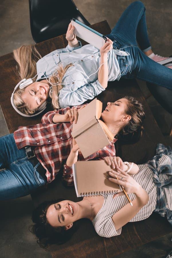 Studenten, die zusammen studieren und auf Tabelle liegen stockfotografie