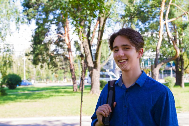 Studenten dragende rugzak bij één schouder en het glimlachen Buitenportret bij park Klaar te bestuderen royalty-vrije stock afbeeldingen