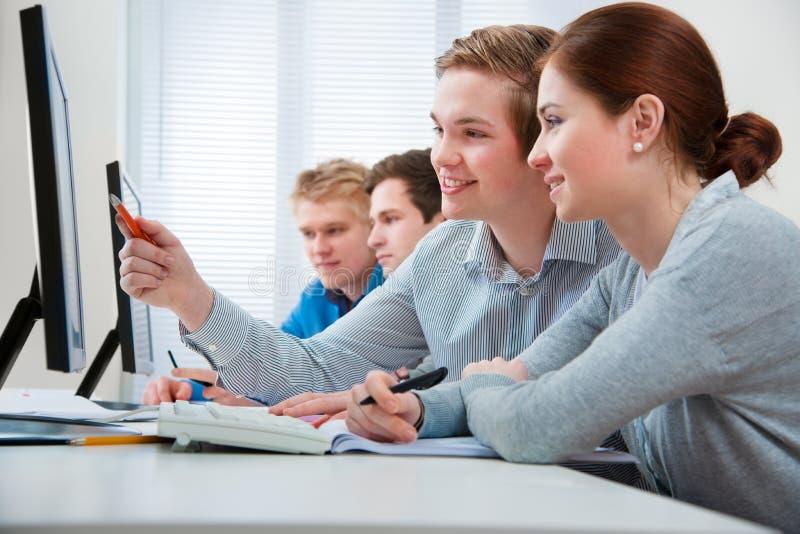 Studenten in een computerklaslokaal stock afbeelding