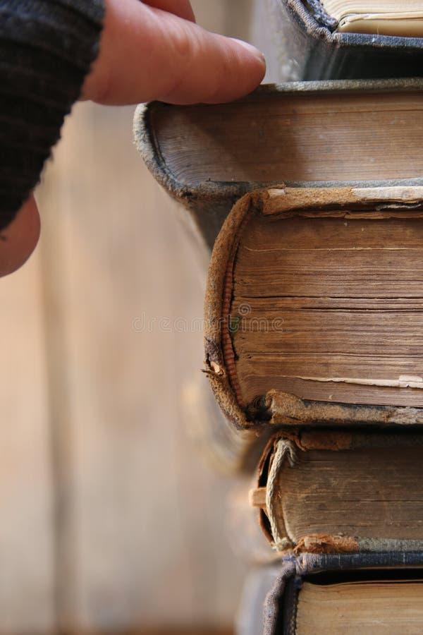 studenten eller forskaren tar boken på en hylla i arkivet, den mjuka fokusen, tappningstil royaltyfri fotografi