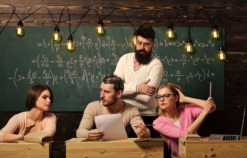 Studenten, Gruppe verbindet das Sprechen, das Bitten um Rat oder den Betrug während der Lehrer, der sie aufpasst Bärtiger Lehrer, stockfoto