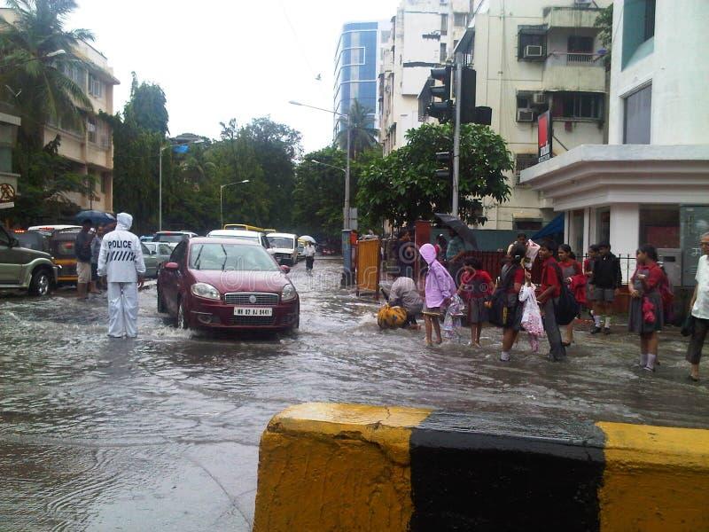 Studenten haben Spaß an einem Regentag auf überschwemmter Mumbai-Straße stockfotos