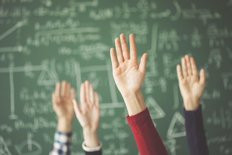 Studenten hoben übergibt oben grünes Kreidebrett im Klassenzimmer an stockfotos