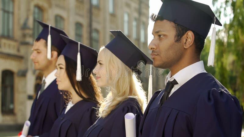 Studenten im Aufbaustudium im akademischen Insignienschlangestehen und Hören auf Rede stockfotografie