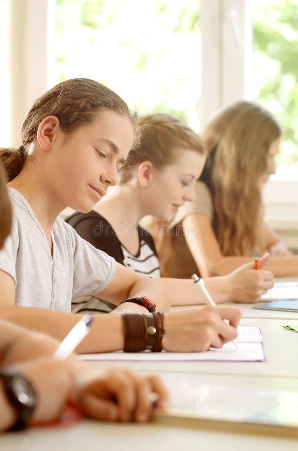 Studenten of leerlingen die test die in school schrijven worden geconcentreerd stock afbeelding
