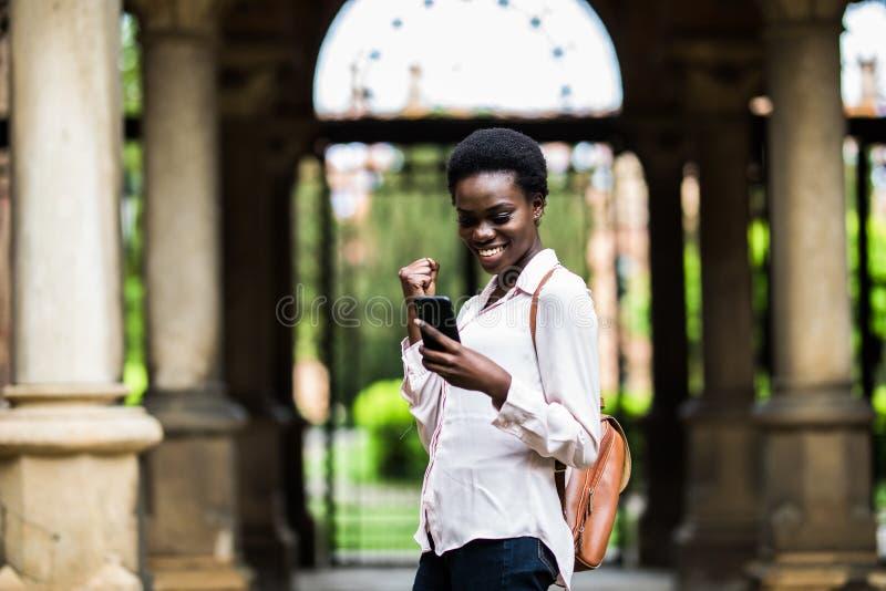 Studenten-Mädchenuniversität der jungen Schönheit afroe-amerikanisch draußen gelesen von den Telefonguten nachrichten der Durchla stockfoto