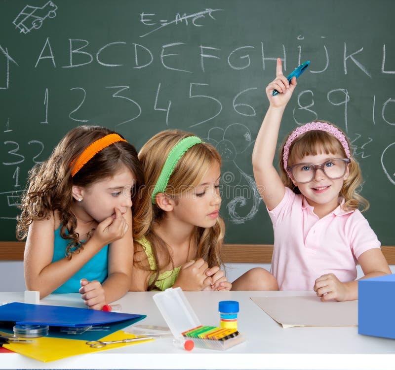 Studenten met knap kinderenmeisje dat hand opheft stock foto