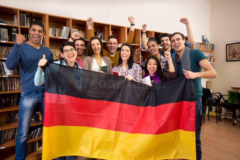 Studenten met opgeheven handen en het glimlachen gezichten huidige Duitse coun royalty-vrije stock afbeelding