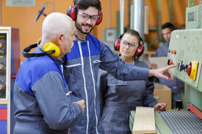 Studenten mit älterem Lehrer durch Holzbearbeitungsmaschine stockbild