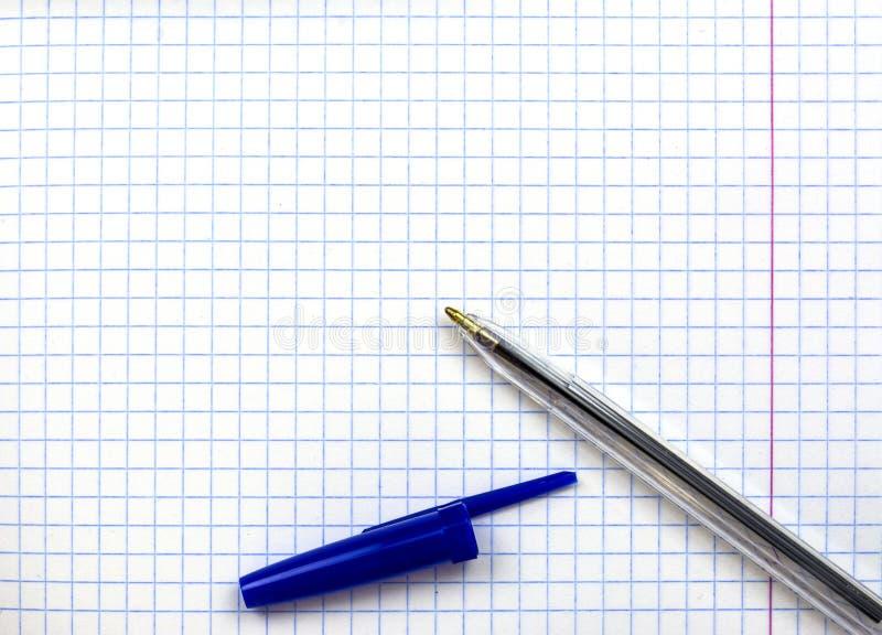 Studenten` s notitieboekje in een kooi Op het blad is een pen stock foto