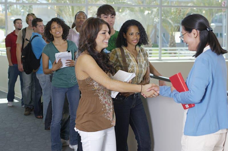 Studenten-Shaking Hands With-Lehrer stockbilder
