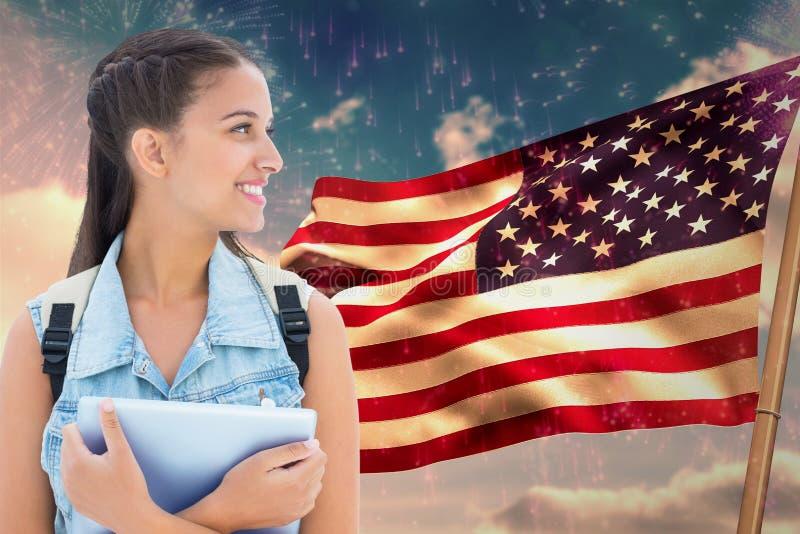 studenten som bär en påse, rymmer en minnestavladator mot amerikanska flaggan royaltyfria foton