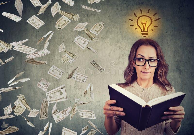 Studenten som läser en bok, har en ljus idé hur man tjänar pengar arkivbild