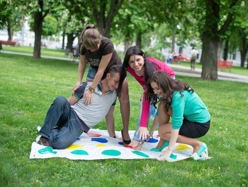 Studenten spielen ein Spiel im Park Twister lizenzfreies stockfoto