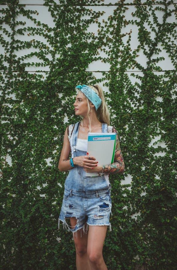 Studenten står vid väggen med gröna växter som väntar på grupper i biologi modern flicka Modell av tatueringar royaltyfri fotografi