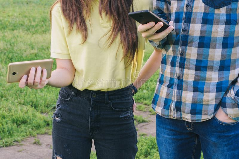 Studenten status buiten en het houden smartphones royalty-vrije stock fotografie