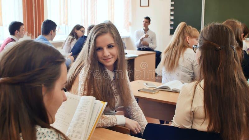 Studenten stehen zwischen den Lektionen in Verbindung, die an einem Schreibtisch sitzen Russische Schule lizenzfreie stockfotografie