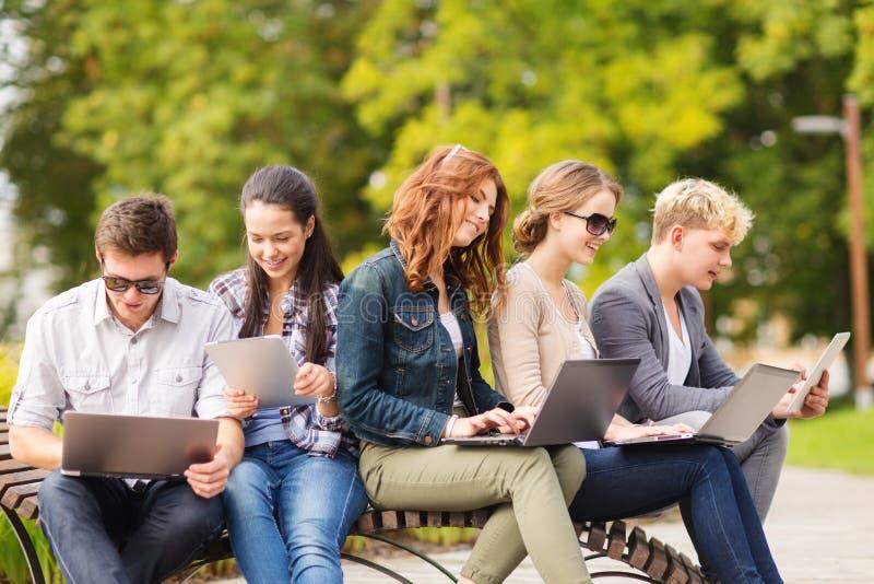 Studenten of tieners met laptop computers stock afbeeldingen