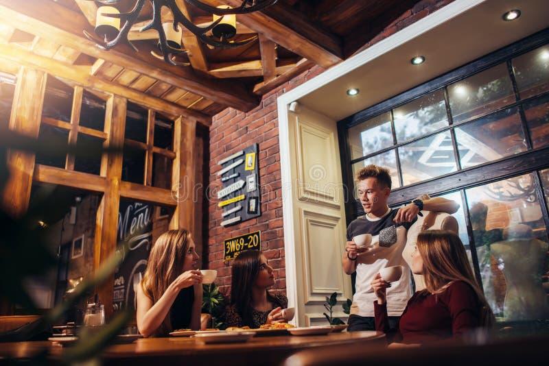 Studenten, welche die zufällige Kleidung trinkt einen trinkenden Kaffee der Mittagspause hört auf ihren männlichen Freund spricht lizenzfreies stockfoto