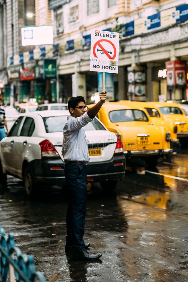 Studentenaktivisten, die friedlich nach 'Ruhe, kein Horn 'auf der Straße mit gelben Taxis im Hintergrund in Kolkata, Indien verla stockbild
