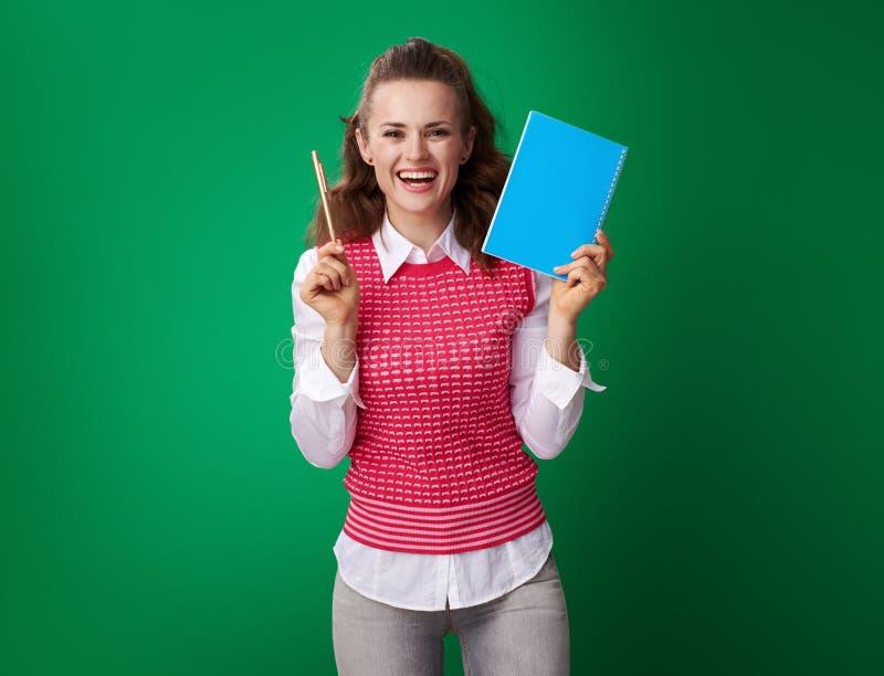 Studentenfrau, die blaues Notizbuch und Stift auf grünem Hintergrund zeigt lizenzfreies stockfoto