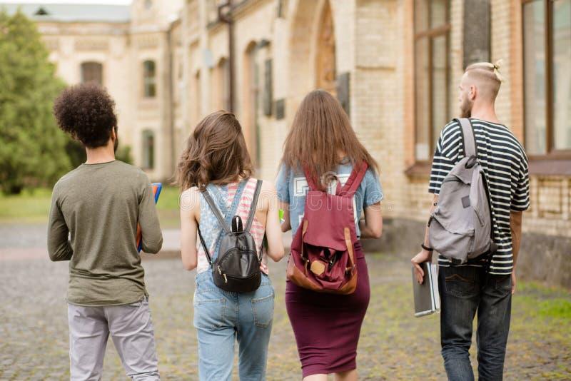 Studentenfreunde, die zusammen zur Universität gehen stockfotografie