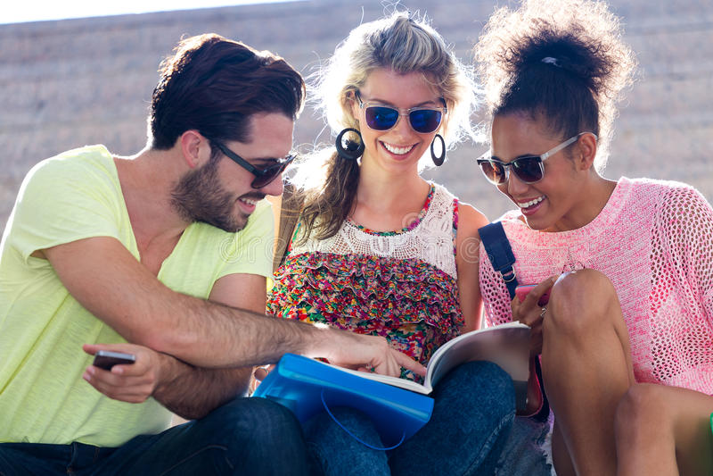 Studentengroep die een boek in de straat bekijken stock afbeeldingen