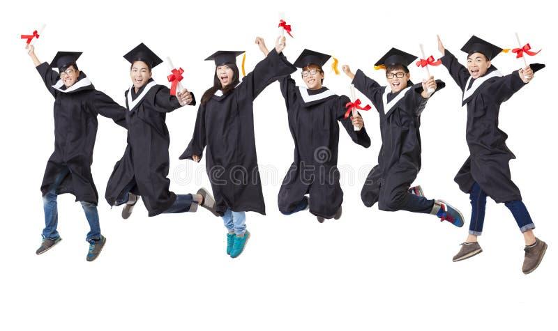 studentengroep die in gediplomeerde robe samen springen stock foto
