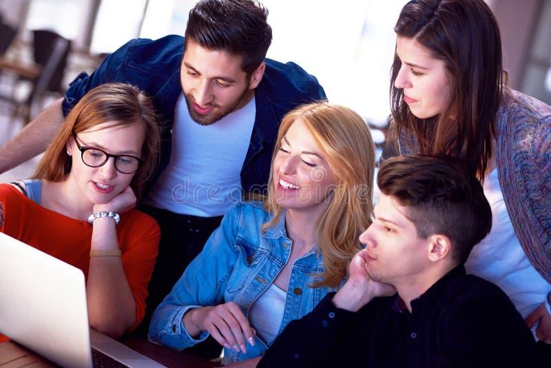 Studentengruppe, die zusammen an Schulprojekt arbeitet stockbild