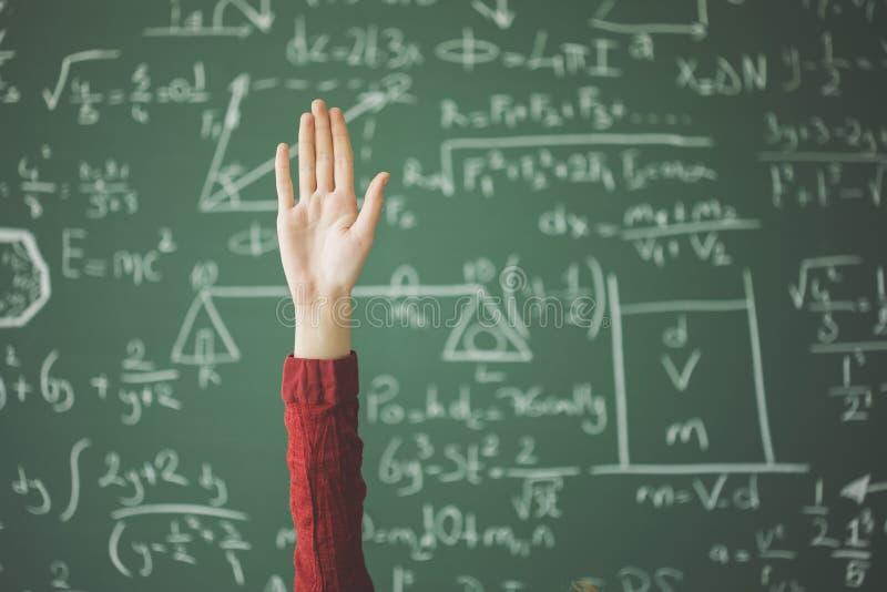Studentenhand omhoog achter groen schoolbord royalty-vrije stock foto