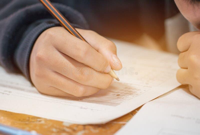 Studentenhanden die examens nemen, schrijvend onderzoeksruimte met holdingspotlood op optische vorm van gestandaardiseerde test m stock foto