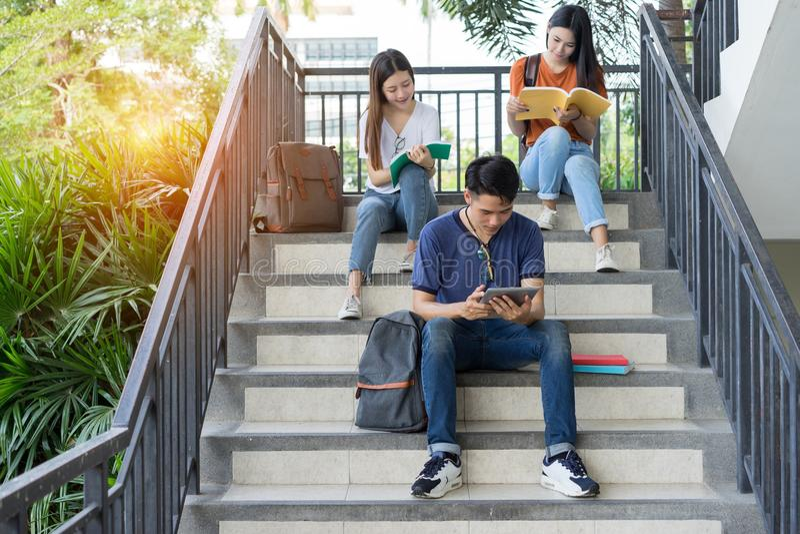 Studentenhochschulasiat, der zusammen Buchstudie liest stockfotos