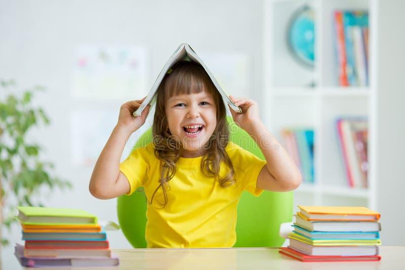 Studentenjong geitje met een boek over haar hoofd stock foto's