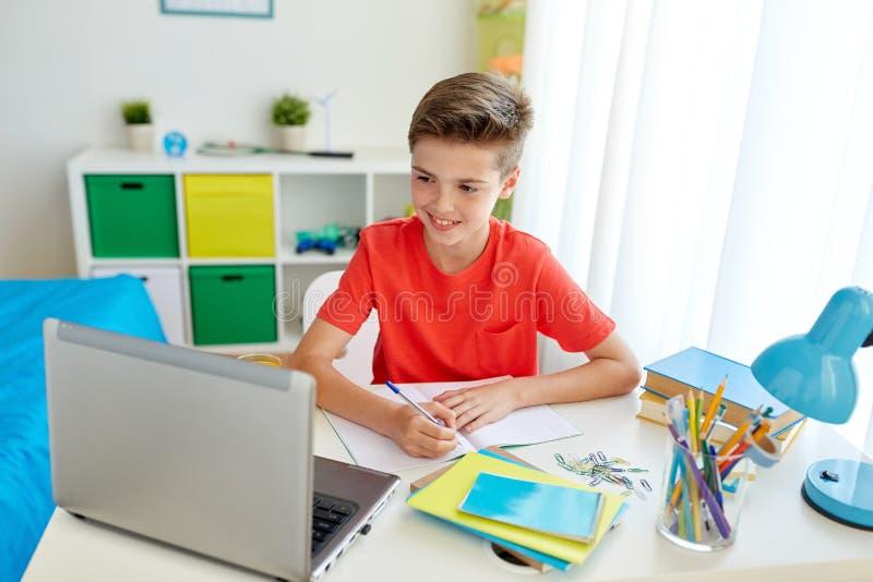 Studentenjongen die met laptop aan notitieboekje schrijven royalty-vrije stock afbeeldingen