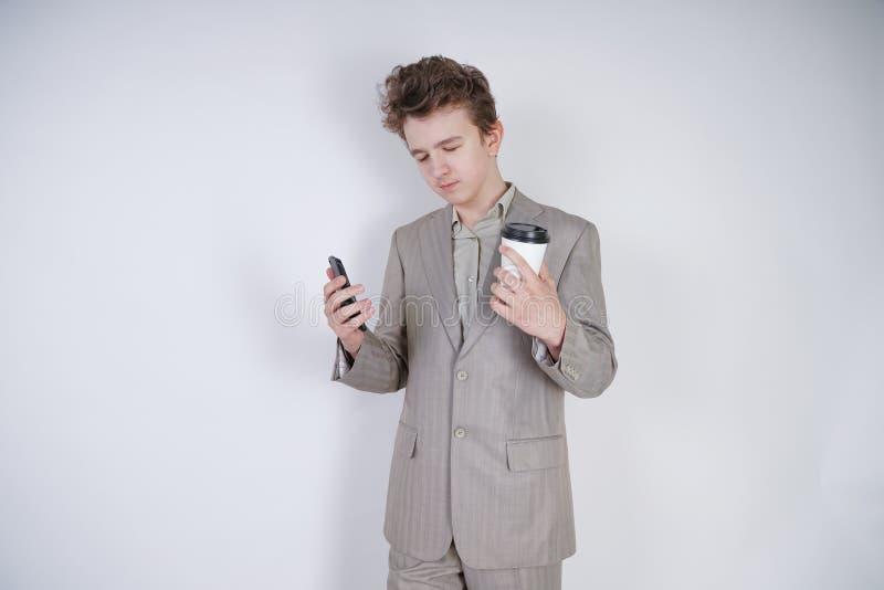 Studentenjugendlich-Jungenstellung mit geschlossenen Augen mit Kaffee und Smartphone sehr müder junger männlicher tragender Anzug stockbilder