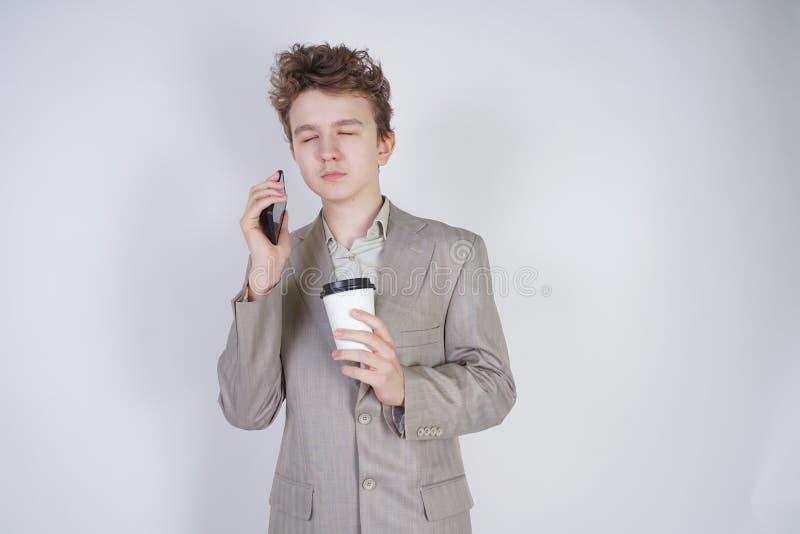 Studentenjugendlich-Jungenstellung mit geschlossenen Augen mit Kaffee und Smartphone sehr m?der junger m?nnlicher tragender Anzug lizenzfreie stockfotografie