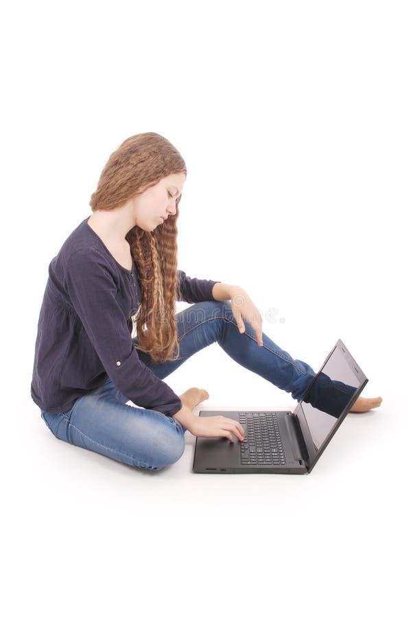 Studentenjugendliche, die seitlich auf dem Boden mit Laptop sitzt lizenzfreie stockfotografie