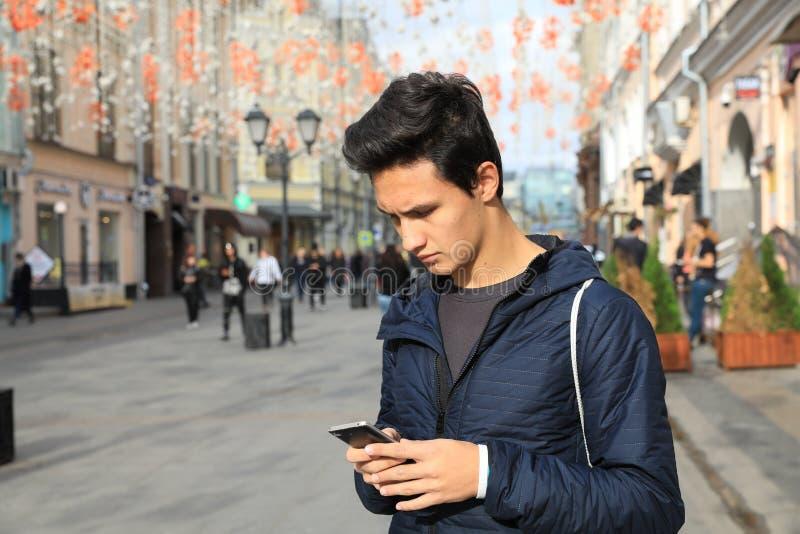 Studentenjunge, der digitalen Tablet-Computer oder bewegliches intelligentes Phon verwendet stockfotografie