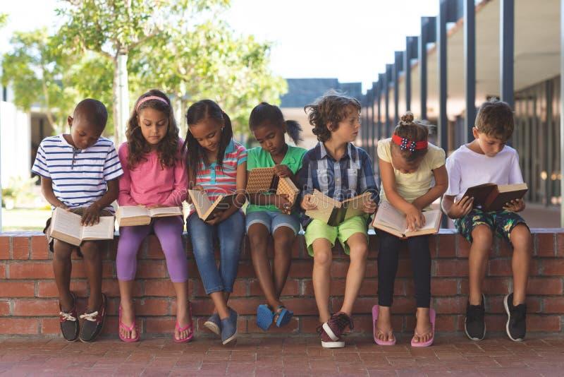 Studentenlesebuch beim Sitzen auf Backsteinmauer am Korridor lizenzfreies stockfoto
