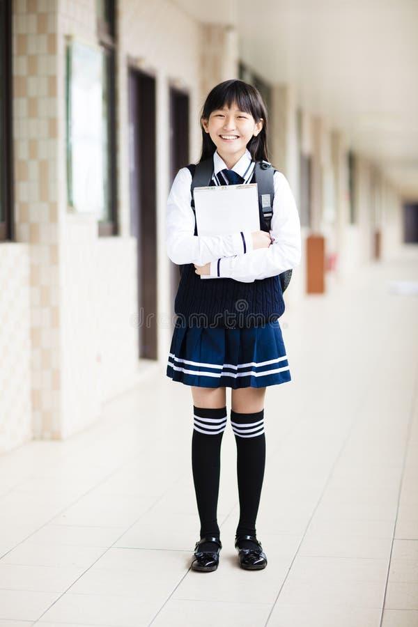 Studentenmädchen, das Bücher vor Klassenzimmer hält lizenzfreies stockbild