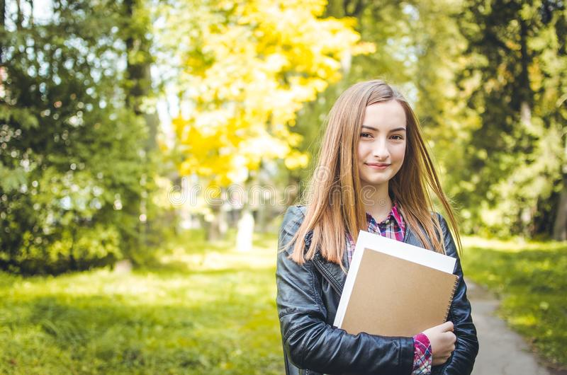 Studentenmädchen, das draußen zurück zur Schule und zum Lächeln geht stockbild