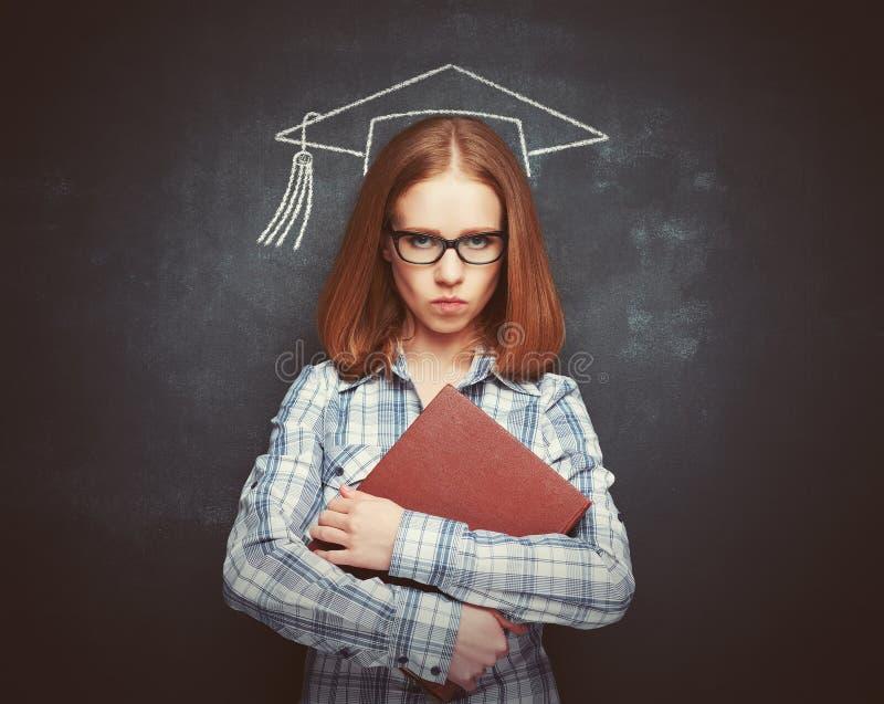 Studentenmädchen in der Kappe, in den Gläsern und in einem Buch an der Tafel lizenzfreies stockbild