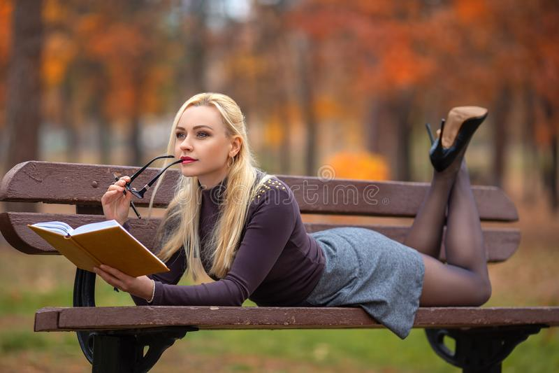 Studentenmädchen-Lesebuch im Herbstpark lizenzfreies stockbild