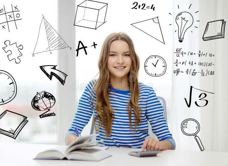 Studentenmädchen mit Buch, Notizbuch und Taschenrechner lizenzfreie stockfotografie
