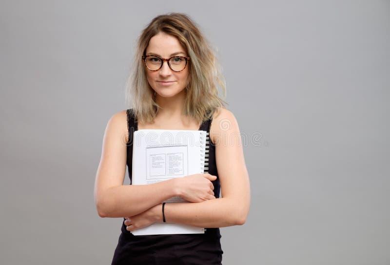 Studentenmädchen mit den Gläsern, die ein Buch halten lizenzfreies stockbild