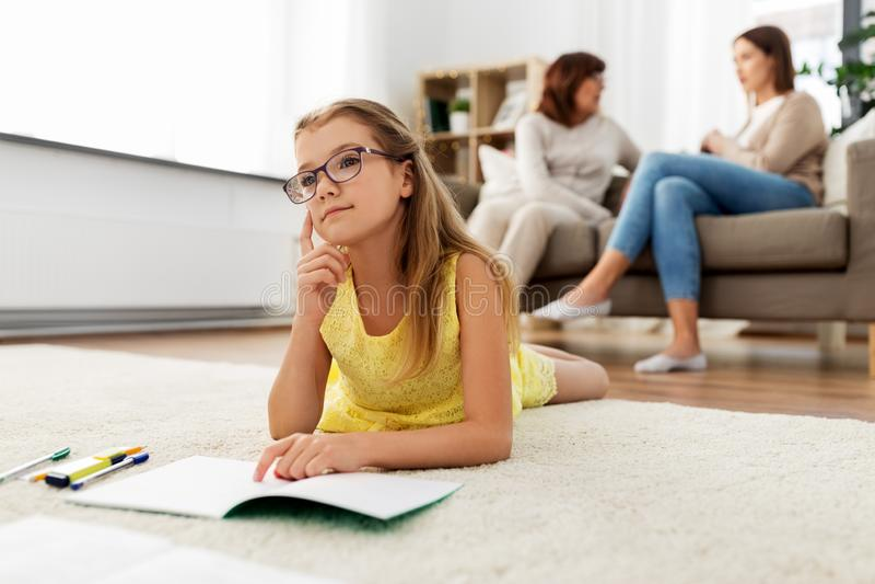 Studentenmädchen mit Notizbuch und zu Hause träumen stockfoto